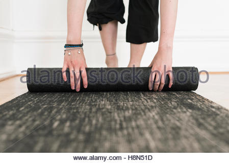 Woman rolling exercise mat - Stock Photo
