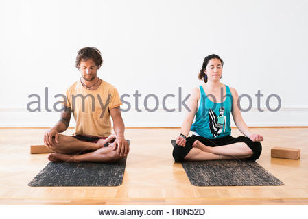 Man and woman practicing yoga in gym - Stock Photo