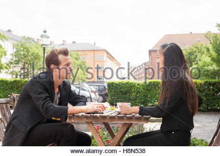 Young woman and man sitting at table and talking - Stock Photo