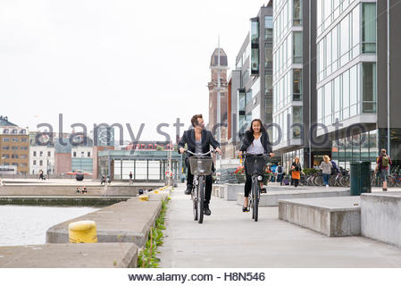Young woman and man cycling by river - Stock Photo