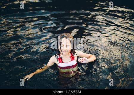 Girl (8-9) in swimming costume standing in water - Stock Photo