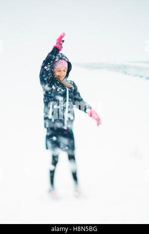 Girl (10-11) playing in snow - Stock Photo