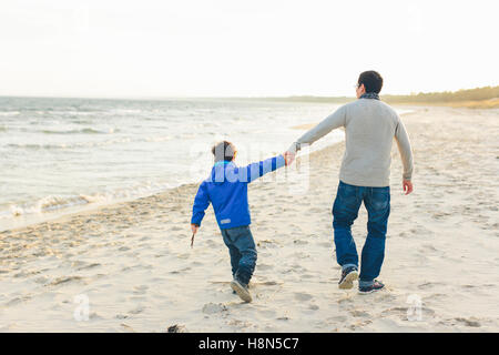 Rear view of father and son (8-9) walking on beach - Stock Photo
