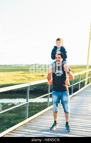 Portrait of father giving son (8-9) piggyback ride - Stock Photo
