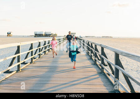 Father with daughter (10-11) and son (8-9) running along boardwalk - Stock Photo