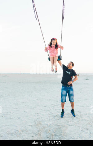 Father pushing daughter (10-11) on swing at beach - Stock Photo