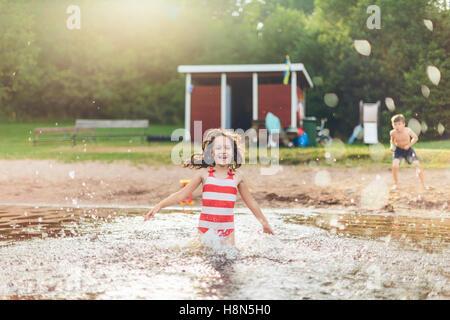 Girl (8-9) splashing water and boy (6-7) standing on ground - Stock Photo
