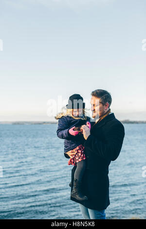 Father with daughter (4-5) standing by sea