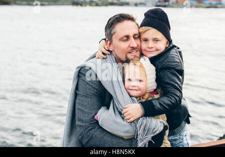 Father with two children (2-3, 6-7) by lake - Stock Photo