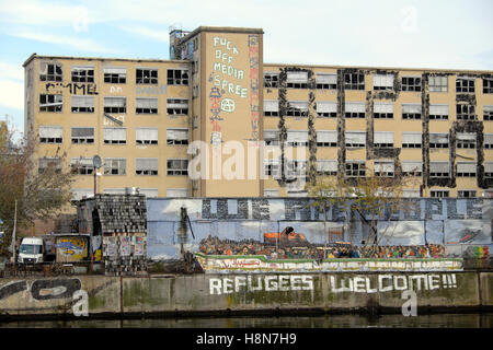 'Refugees Welcome' graffiti on the riverbank wall 'We Are People' sign by the River Spree in Friedrichshain, Berlin - Stock Photo