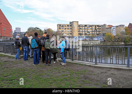 Tour group tourists gather opposite 'Refugees Welcome' sign on the riverbank wall of the Spree in Friedrichshain, - Stock Photo