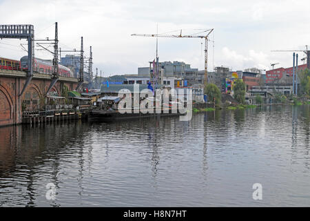Kater Blau Blue Cat nightclub site cityscape and train travelling over bridge by the river Spree in Friedrichshain - Stock Photo
