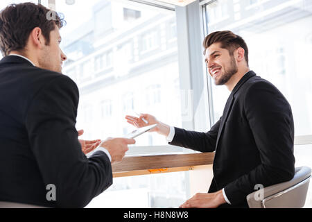 Two cheerful young businessmen using tablet on business meeting in office - Stock Photo