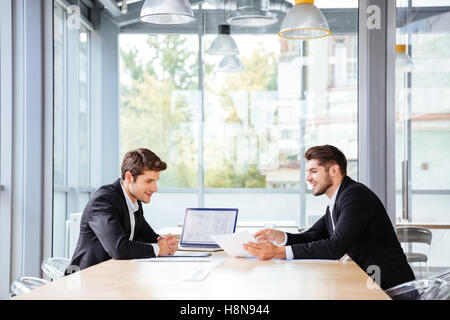 Two happy young businessmen working together using laptop on business meeting in office - Stock Photo