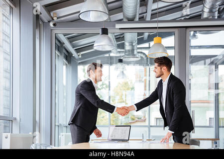 Two happy successful young businessmen standing and shaking hands on business meeting - Stock Photo