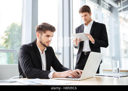Two concentrated young businessmen working with laptop and tablet in office - Stock Photo