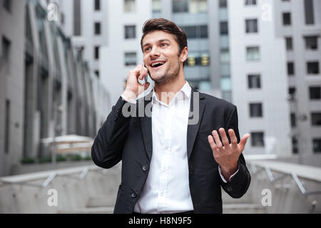 Happy young businessman standing and talking on mobile phone in the city - Stock Photo