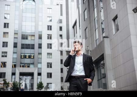 Smiling young businessman talking on mobile phone in the city - Stock Photo