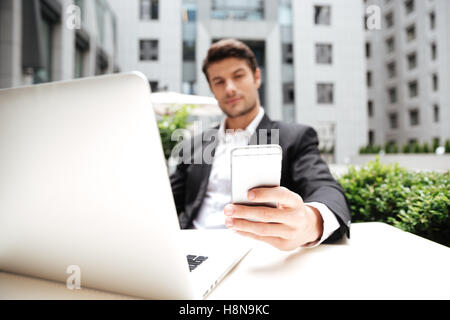 Attractive young businessman using laptop and cell phone in outdoor cafe - Stock Photo