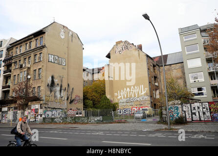 Derelict buildings with graffiti next to new apartment building property on Kopenicker Strasse, Kreuzberg, Berlin - Stock Photo