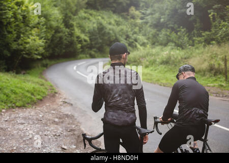 Two road cyclists having a break in Cheddar George - Stock Photo