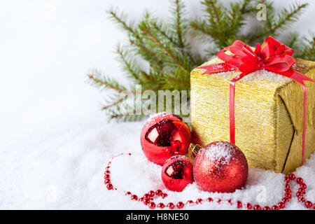 White greeting card with copy space for christmas or new year with golden wrapped gift, fir branches and red ball - Stock Photo