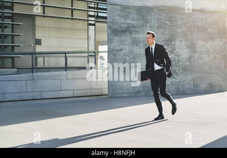 Young businessman in suit holding skateboard at hand and walking in haste down street in sunlight. - Stock Photo