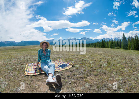 Beautiful young lady sit on a field in the mountains outdoors background. - Stock Photo