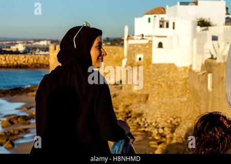 A Young Moroccan Woman Looks Out Over The Walled City Of Asilah At Sunset, Morocco - Stock Photo