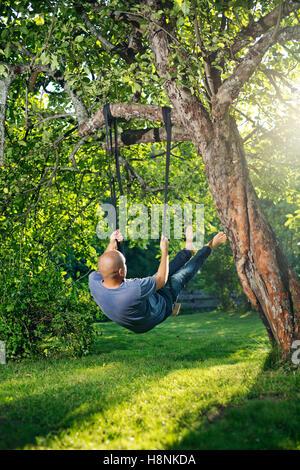 Man swinging on tree swing - Stock Photo