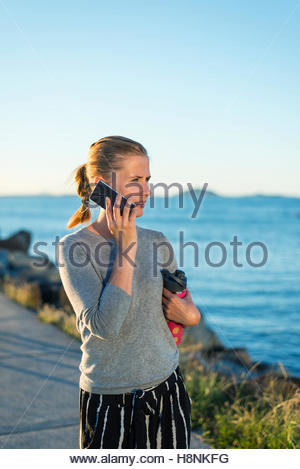 Woman talking on mobile phone, sea in background - Stock Photo