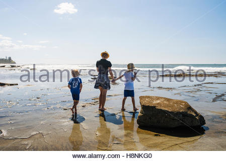 Mid adult woman and two boys (4-5, 6-7) walking on beach - Stock Photo