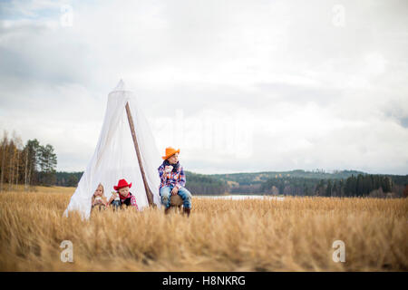 Children (8-9) wearing cowboy hats sitting in tent - Stock Photo