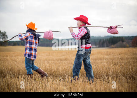 Boys (8-9) wearing cowboy clothes walking in field - Stock Photo