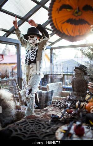 Boy (8-9) wearing skeleton costume raising arms in house - Stock Photo