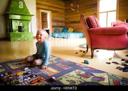 Boy (4-5) kneeling on multi colored carpet in room - Stock Photo
