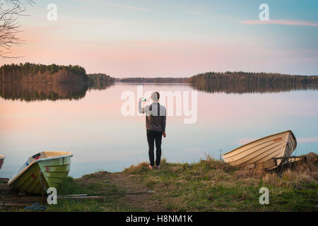 Mid adult man taking pictures on lake shore - Stock Photo