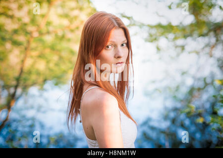 Portrait of young woman in forest - Stock Photo