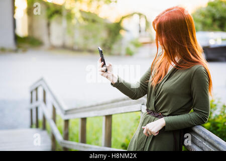 Redhaired woman standing on staircase and using phone - Stock Photo