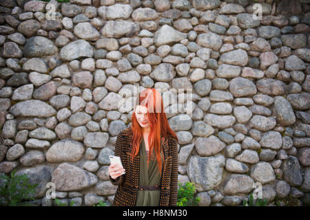 Redhaired woman standing against stone wall and using phone - Stock Photo