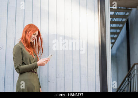 Redhaired woman using phone against white wall - Stock Photo