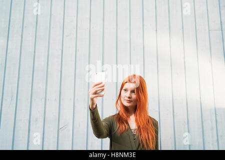 Redhaired woman taking selfie against white wall - Stock Photo