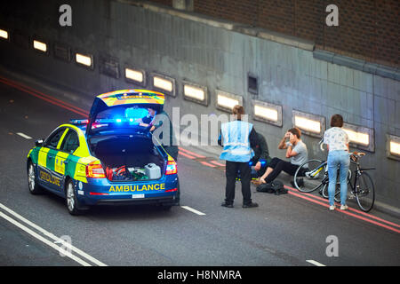 Ambulance medics treating an injured cyclist on the side of the road in London - Stock Photo