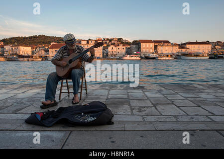 An old sailor playing guitar in the port of Trogir with view of the Island Ciovo (in the background). Trogir, Dalmatia, - Stock Photo