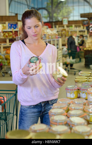 Lady looking at conserves in store - Stock Photo