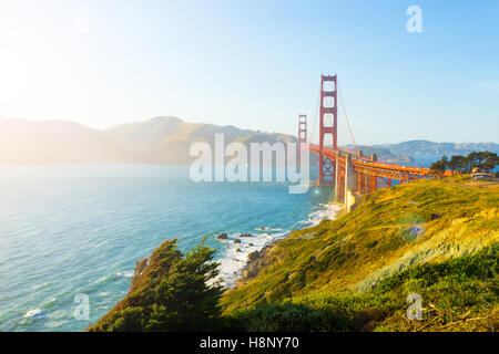 Sunlight provides high key highlights, lens flare over Marin Headlands with Golden Gate Bridge seen over rocky coastline - Stock Photo