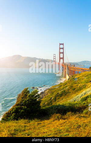 Sunlight provides high key highlights over Marin Headlands with Golden Gate Bridge seen over rocky coastline at - Stock Photo