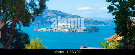 Wide panoramic telephoto view of Alcatraz Federal Penitentiary and island in middle of San Francisco bay framed - Stock Photo