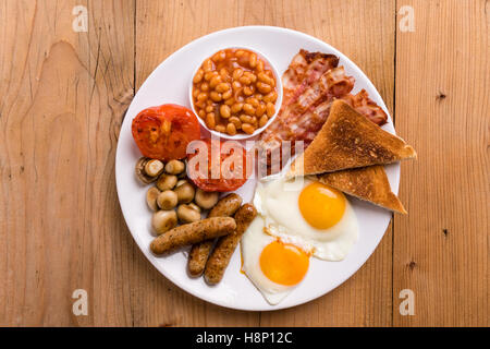 rustic full english breakfast with bacon, sausage, eggs, beans, mushrooms - Stock Photo