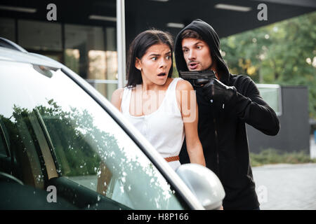 Aggressive man thief in gloves threatening with gun to frightened young woman on car parking - Stock Photo